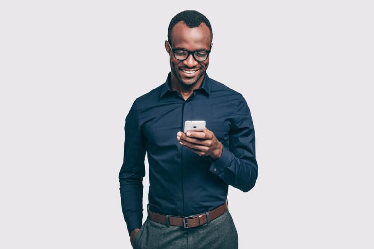 A man smiling while looking down at his phone.