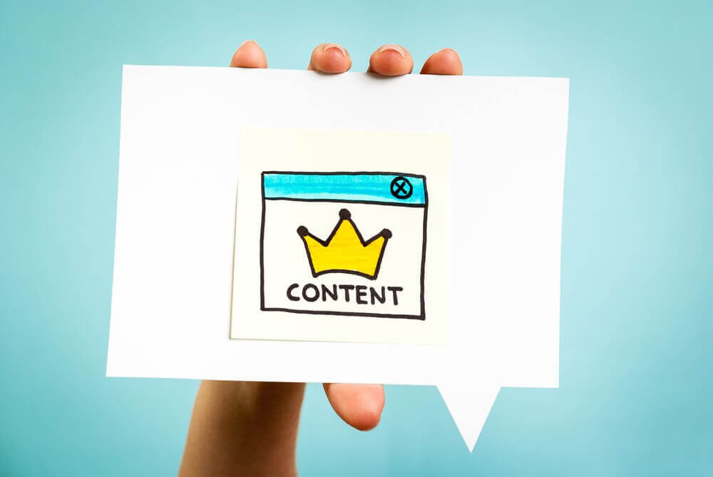 A photograph featuring a web page of a cartoon crown indicating that content is king.