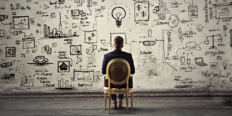 A photograph of a lone man sitting before a wall with his ideas splayed out in front of him in cartoon form.