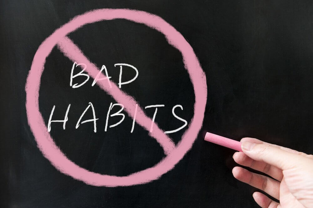 "A photograph of the phrase ""bad habits"" written on a chalk board and crossed out with pink chalk."