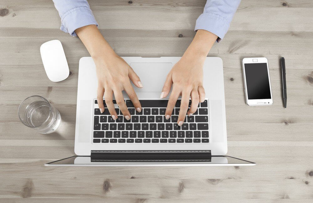 Woman typing on laptop keyword at desk
