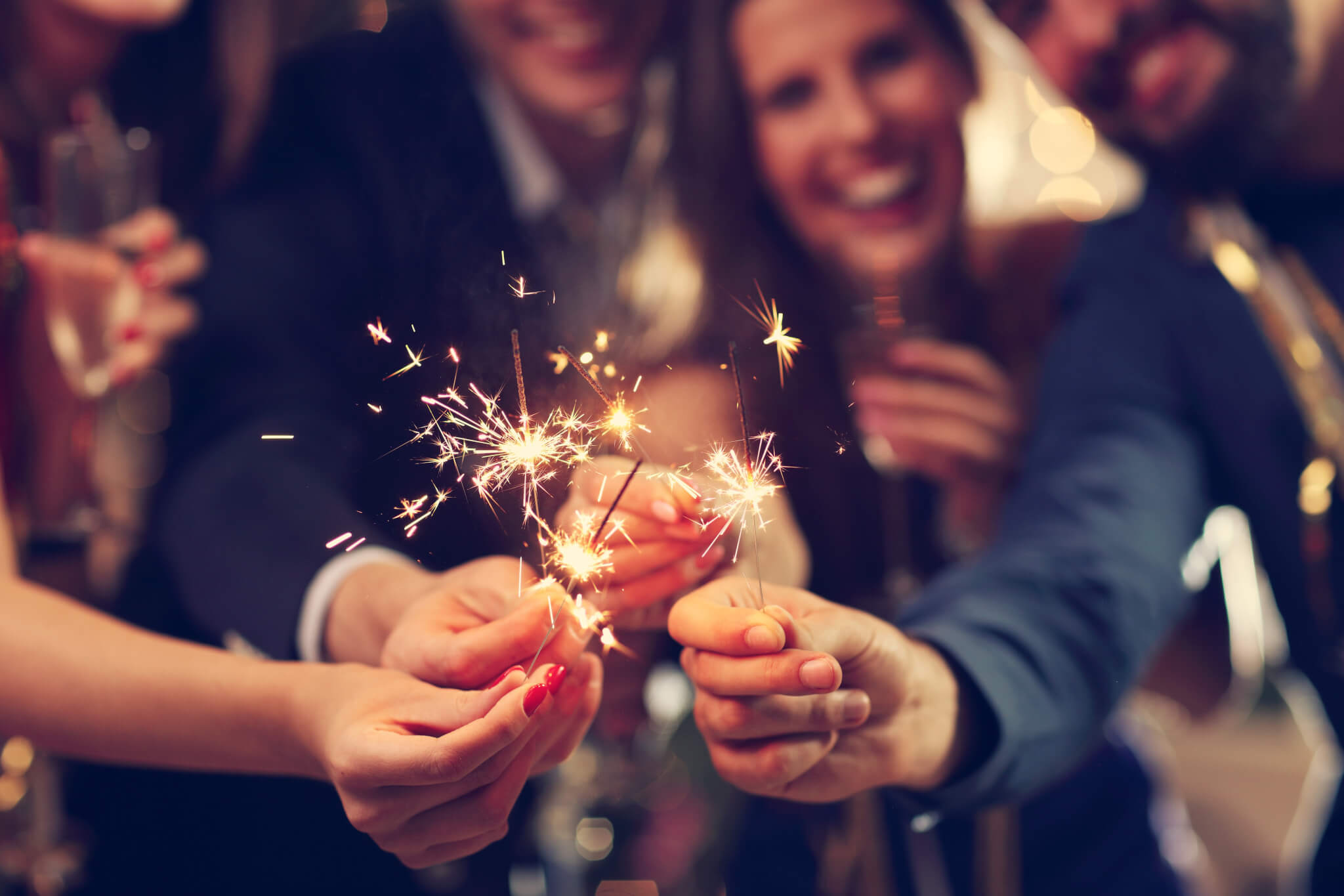 Group of people holding sparklers on New Years Eve