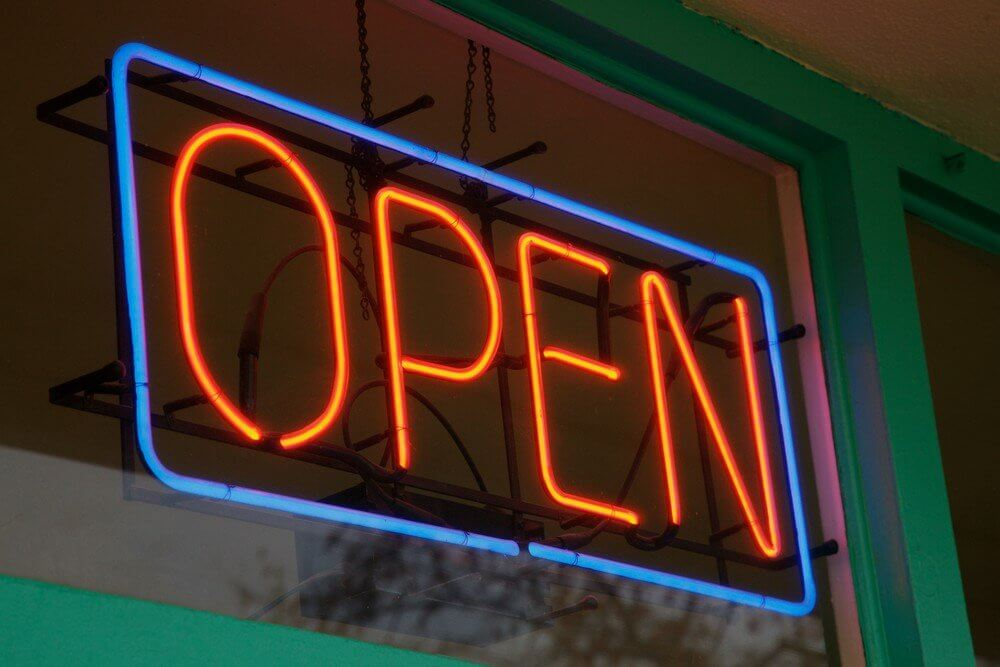 "A photograph of a neon sign reading, ""open""."