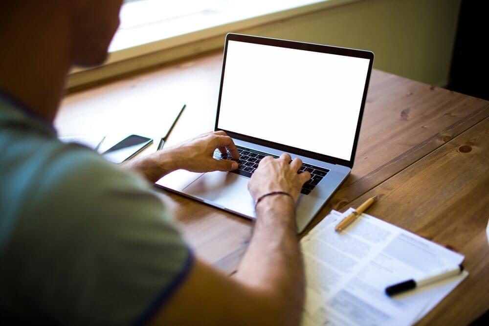 man sitting at laptop writing an article