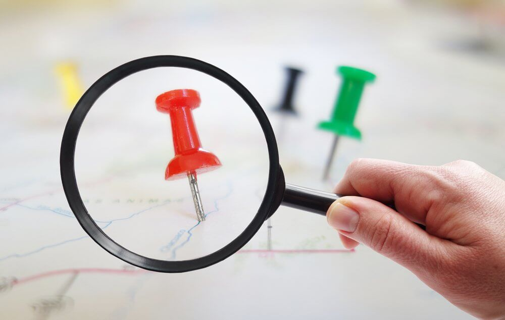 magnifying a push pin on a map symbolizing local search