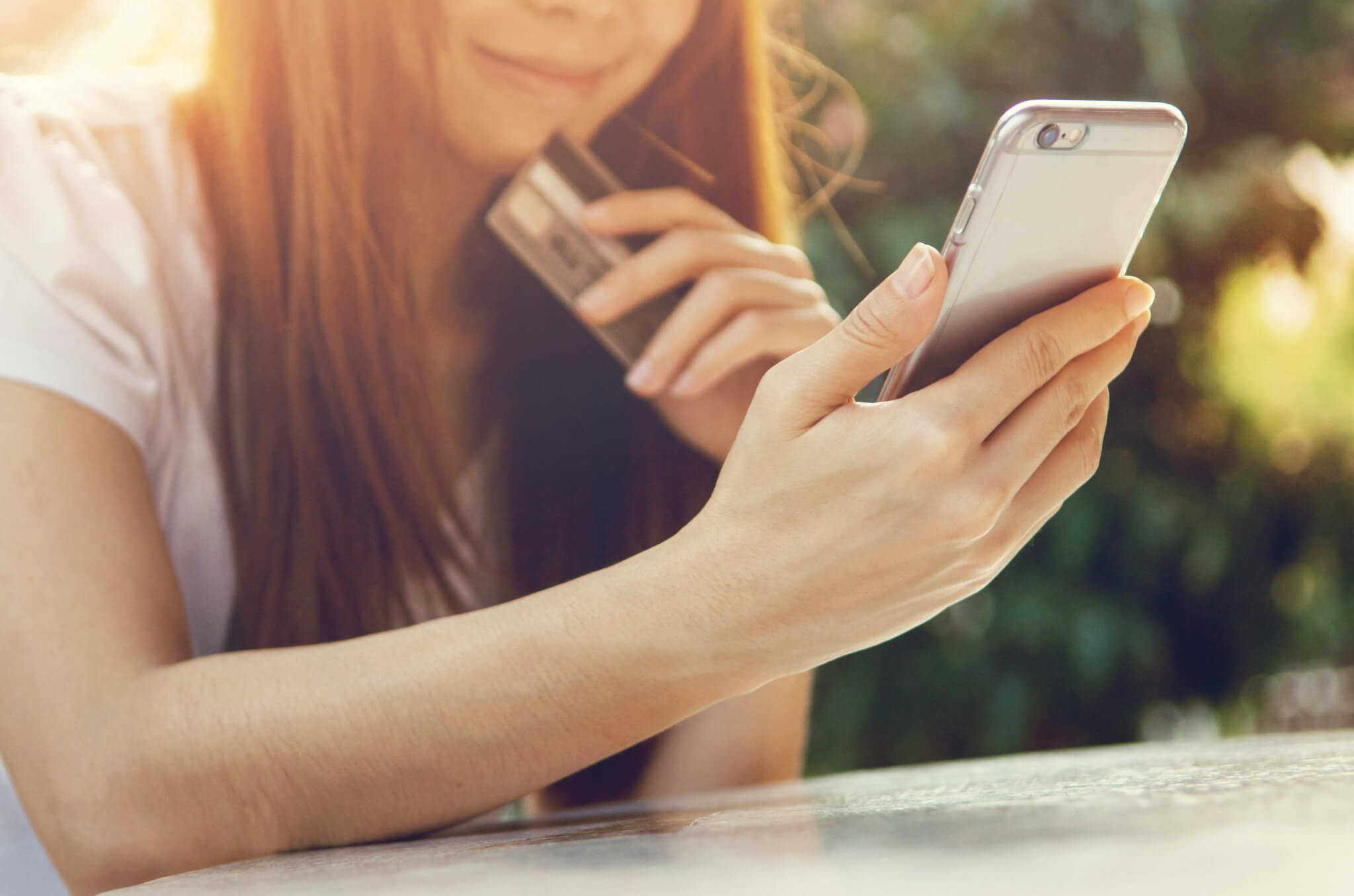 Girl holding iPhone and credit card outside.