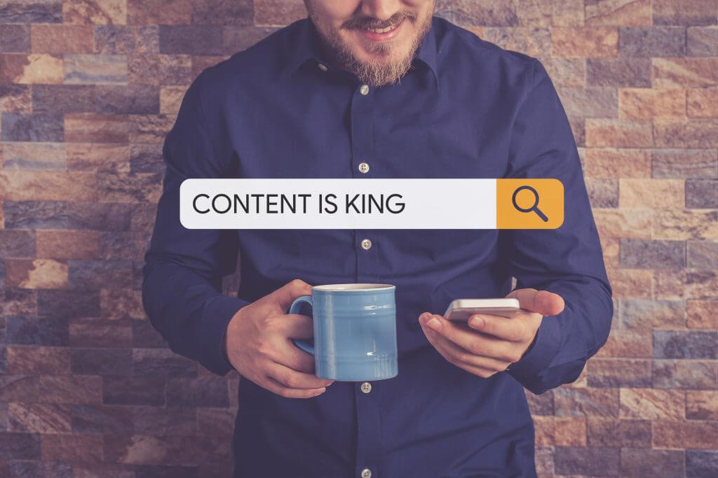 man holding mug and phone with content king