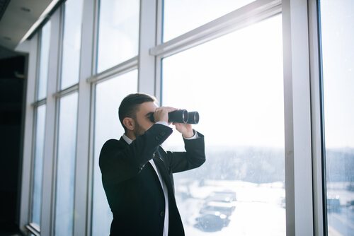 Competitive Keyword research symbolically displayed by a businessman using binoculars to watch competition