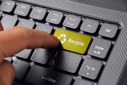 """A man pressing a """"recycle"""" key on a keyboard to symbolize reusing old content"""