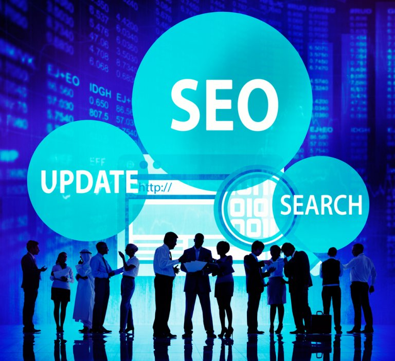 Business people standing in front of computer screen with SEO, Update, & Search Bubbles in the background