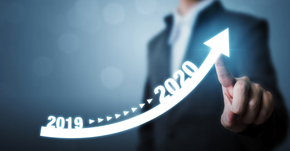 Businessman pointing arrow graph for growth year 2019 to 2020