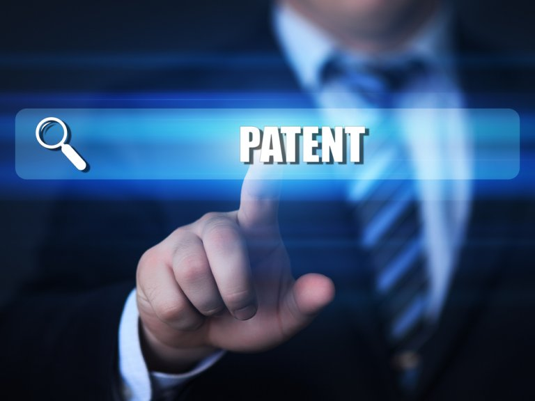 search bar with the word patent in it and a man in a suit behind it pushing his finger on the search bar