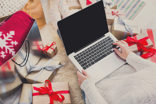 woman on a laptop surrounded by presents