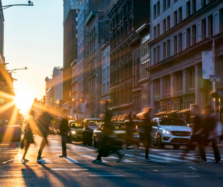 people walking in the street with sun setting