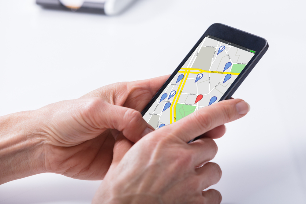 A close up of a person's hands holding a cell phone. The screen displays a map, with a red tag highlighting the person's location. Several blue tags are spread throughout the map to highlight points of interest.