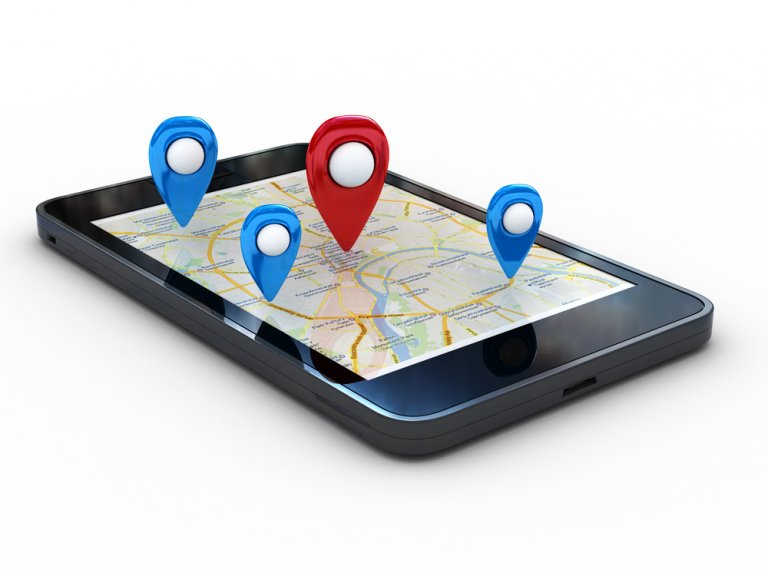 A smartphone laying on a flat white surface. A map is displayed on screen. Several points of interest, marked as red and blue markers, point to the screen.