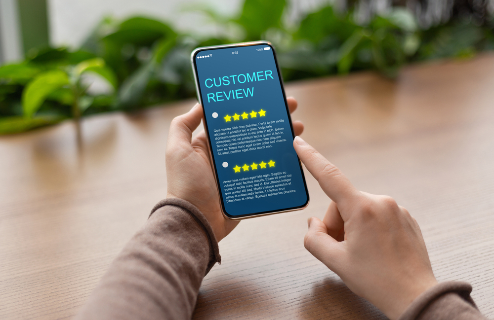 A person's hands are shown scrolling through a smartphone screen on a wooden table. The screen includes a customer reviews page with several five star reviews on it.