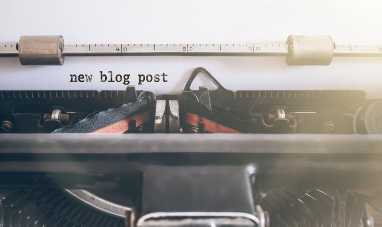 """A close up of a typewriter with a white sheet of paper sticking out. On the paper is printed three words: """"new blog post""""."""