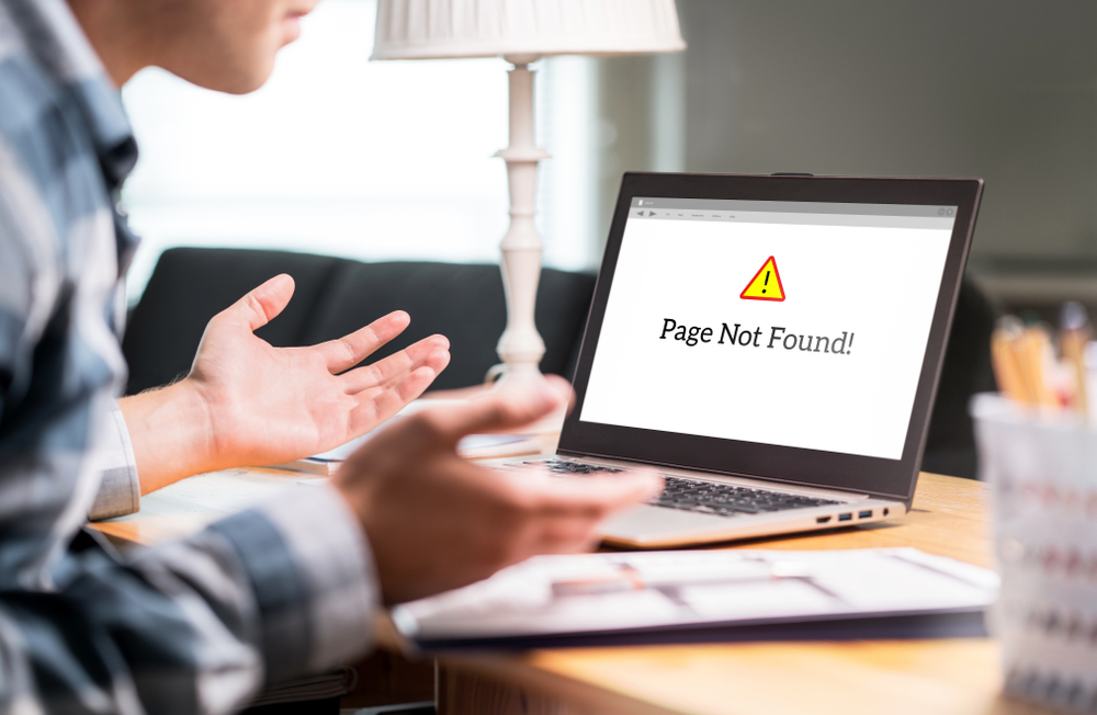 """A man holds his hands to the side in frustration after seeing an error on the laptop screen in front of him. The screen shows a yellow triangle with an exclamation point inside and text under it that reads """"Page not found""""."""