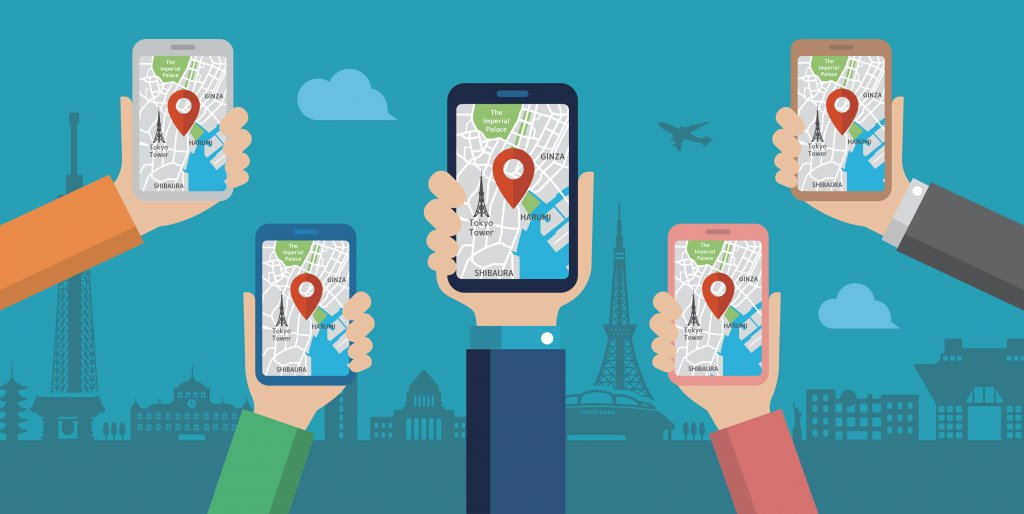 An illustration of five hands with smartphones in them. Each one is displaying the same location on a map. In the background of the image is a city skyline.